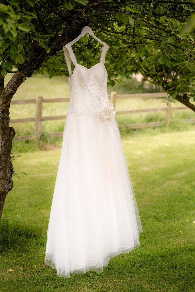 wedding dress hangs from a tree