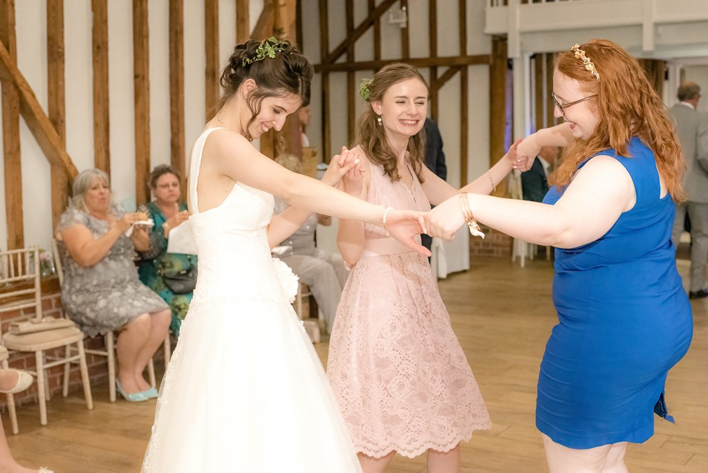 the bride and guests dance together at milling barn