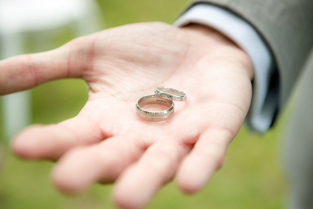 the groom holds out the wedding rings on his hand
