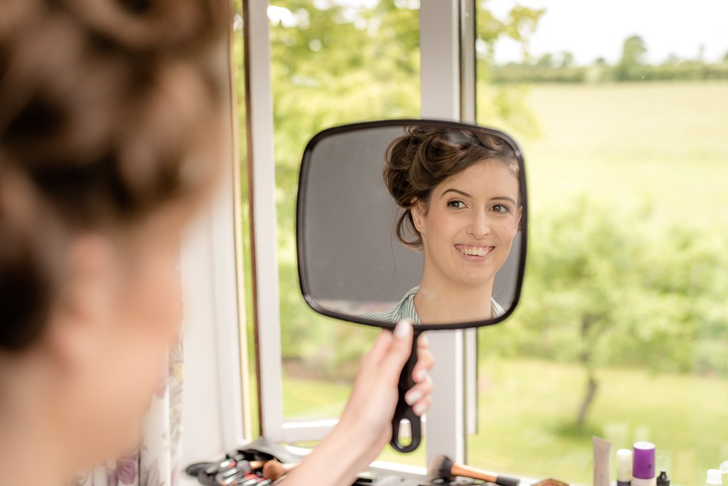 the bride looks at herself in the mirror