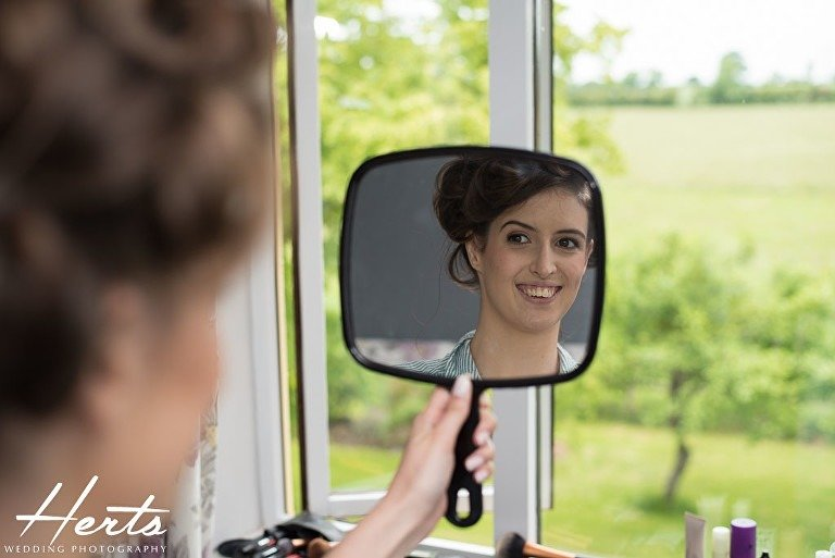 The bride looks at her reflection in the mirror