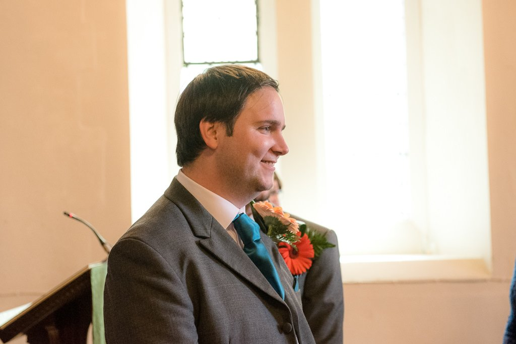 The groom smiles at the bride
