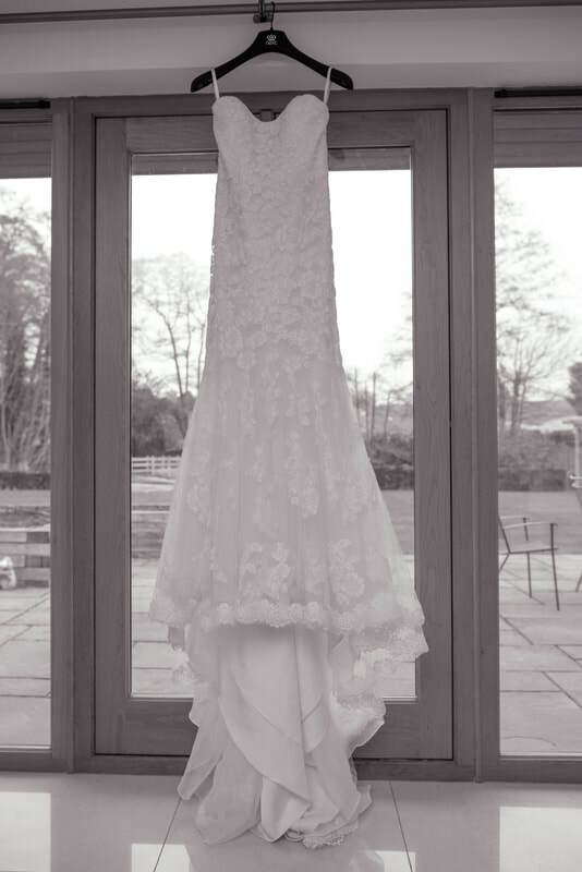 The wedding dress hangs by the sliding doors