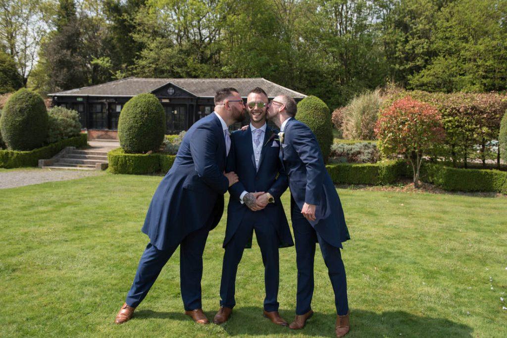 The best men kiss the groom