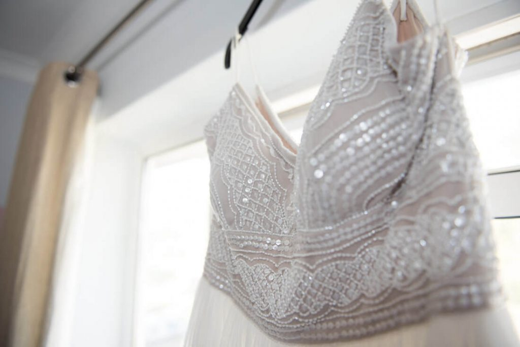 The modern wedding dress hangs from a curtain rail
