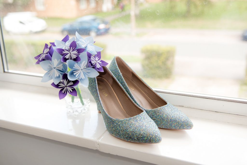 Blue Sparkling wedding shoes placed on a window sill
