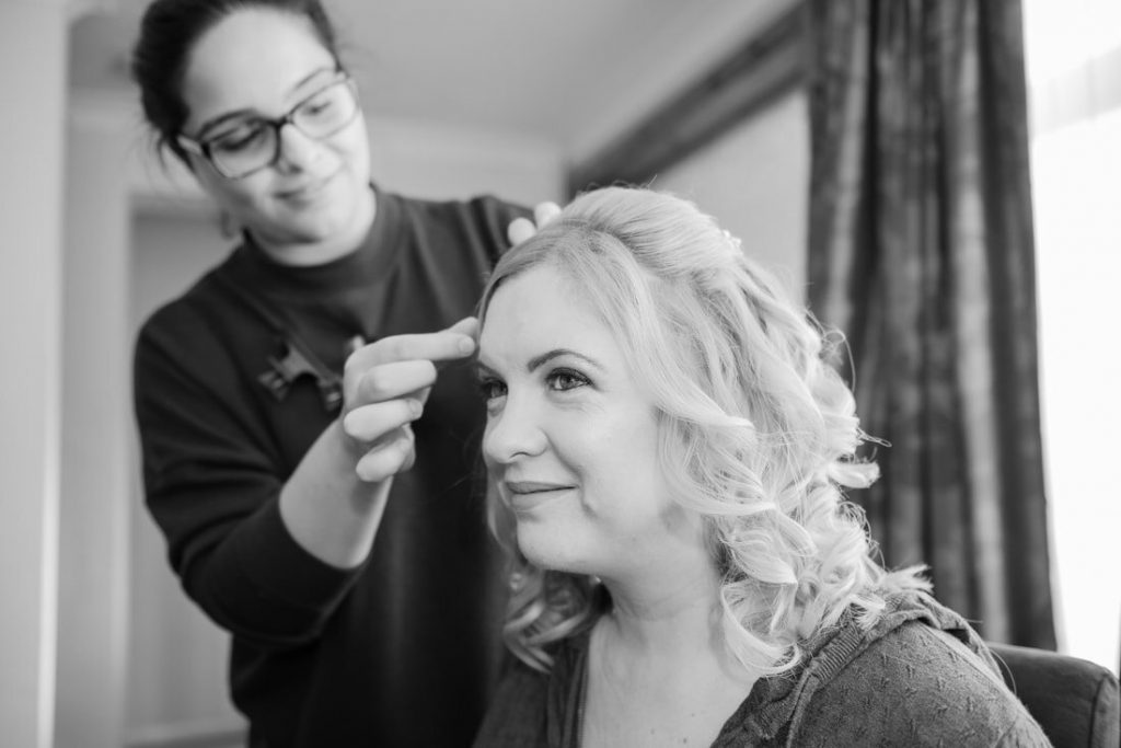 A bridesmaid is being worked upon by an MUA