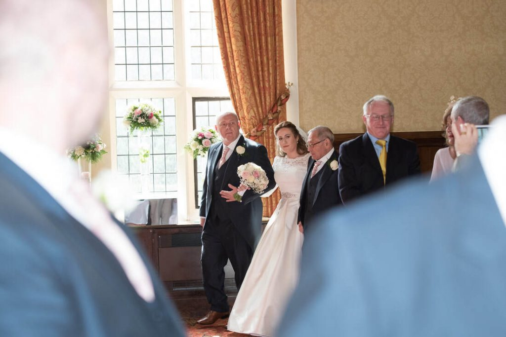 The bride walks in with her father and grandad