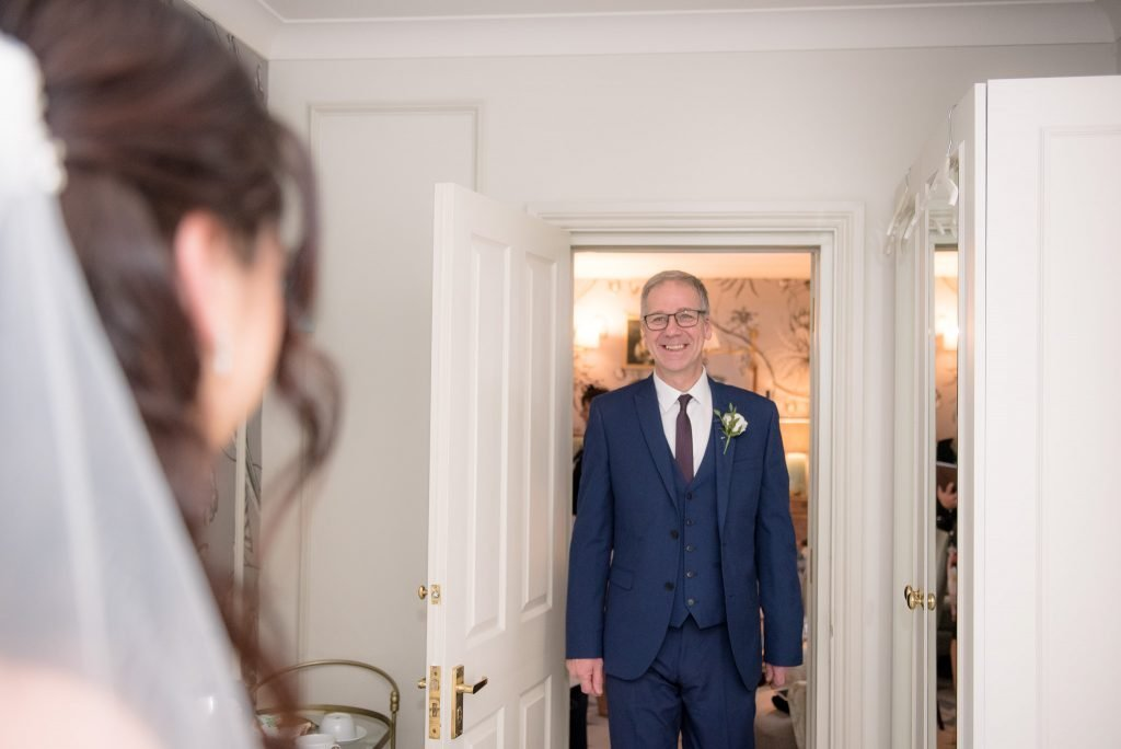 The father of the bride sees his daughter in her wedding dress