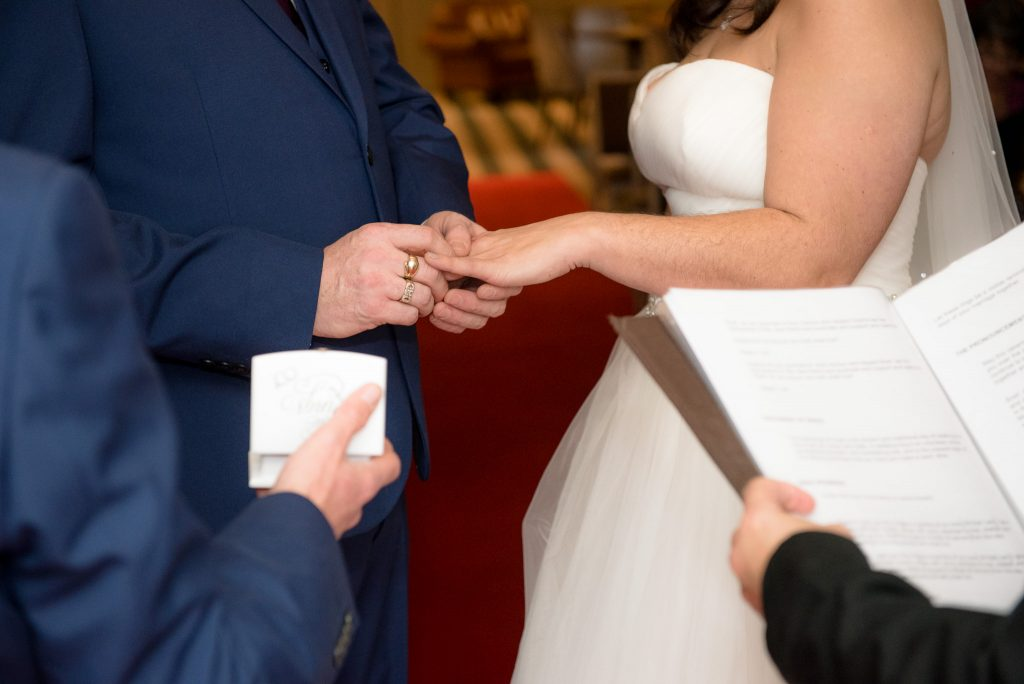 The groom places the wedding ring onto the bride