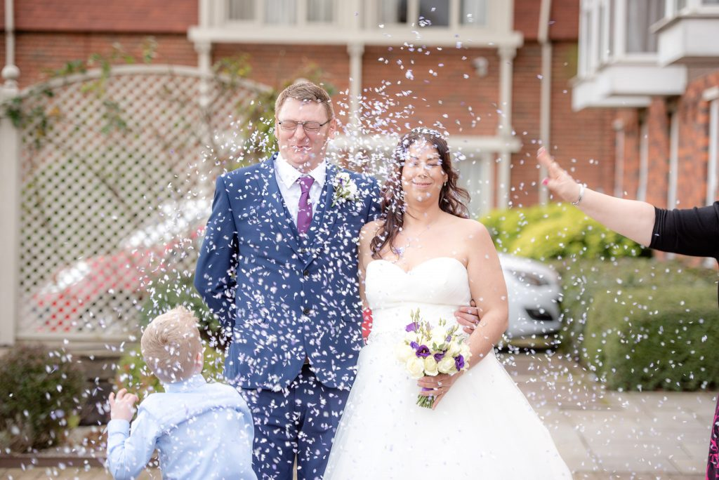 Confetti directly in the face of the bride and groom