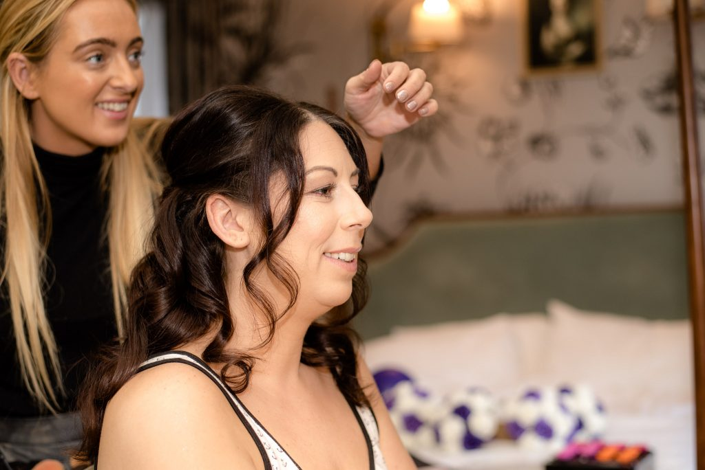 The make up artist styles the hair of the bride