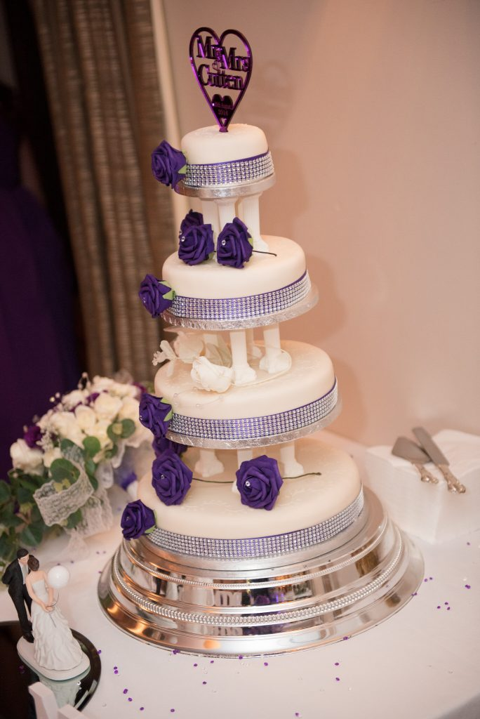 The wedding cake with purple flowers
