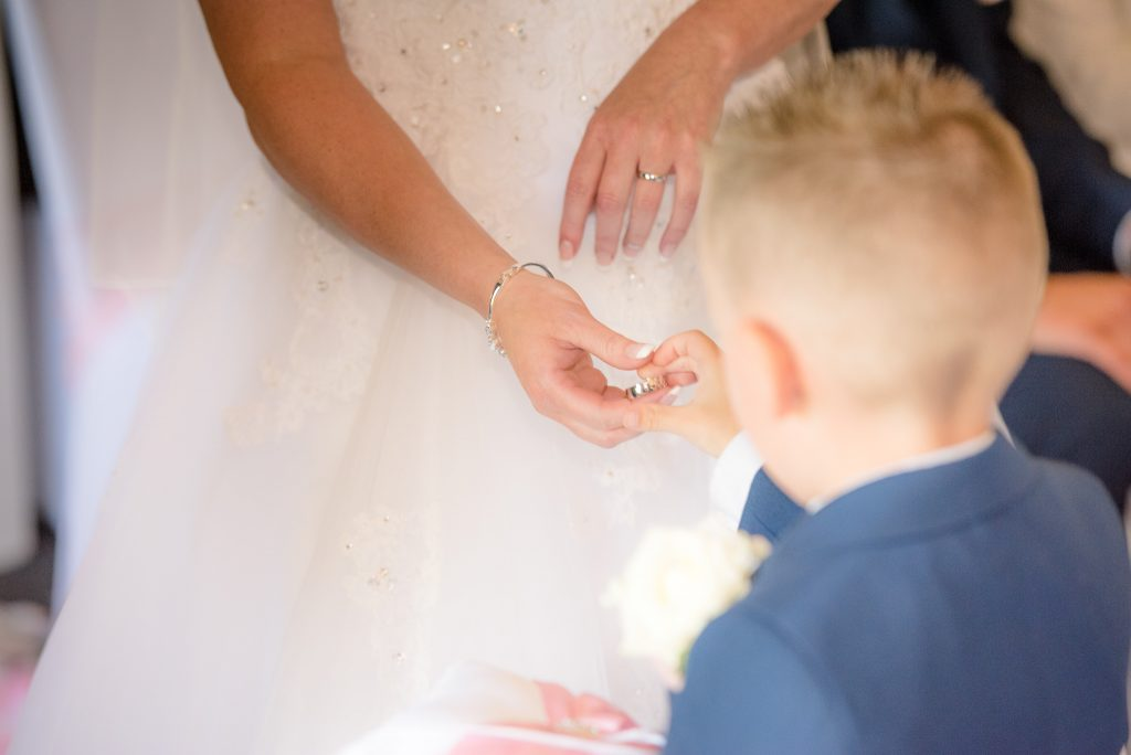 A page boy hands over the wedding rings