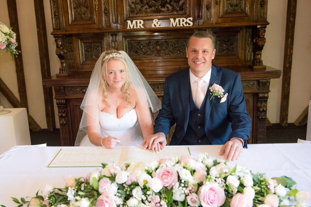 The bride and groom hold hands whilst signing the wedding register
