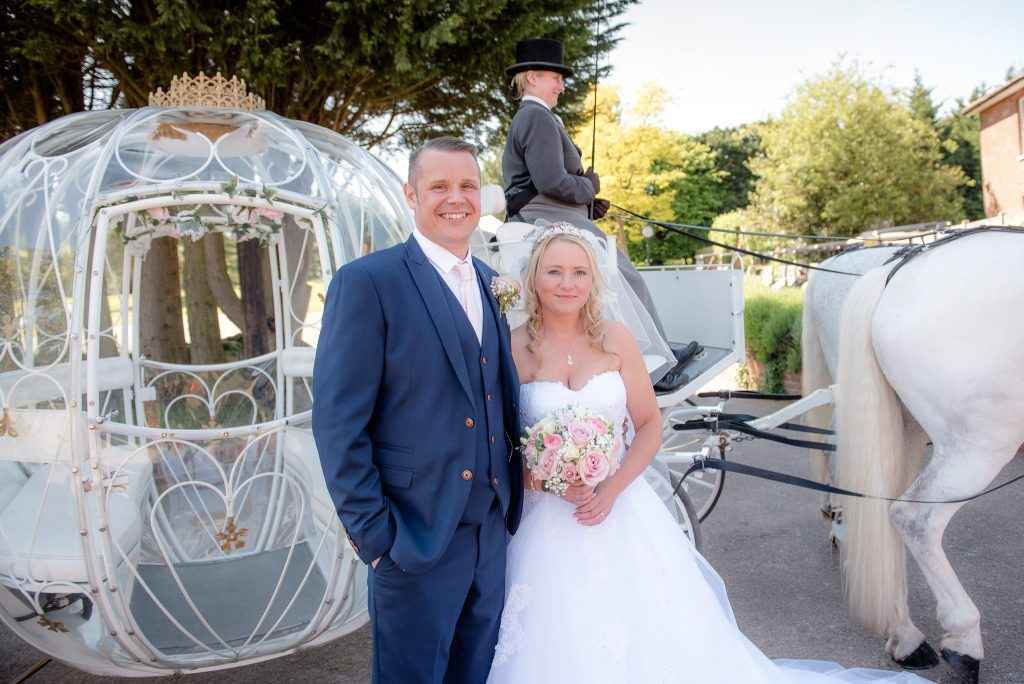 The bride and groom with a horse drawn carriage pictured behind them