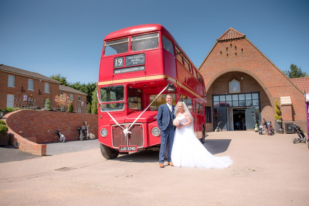 The bride and groom stand in front of the london bus.