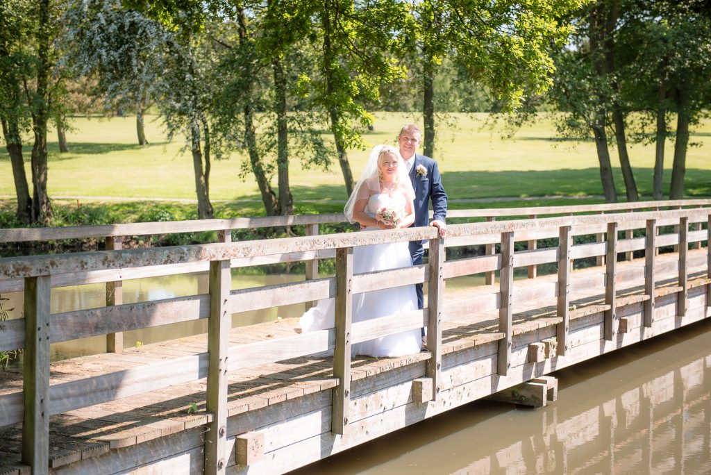 The bride and groom pose on a wooden bridge