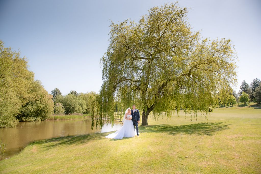 The bride and groom shaded under a willow tree