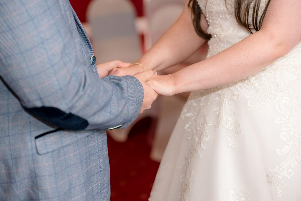 The bride and groom hold hands
