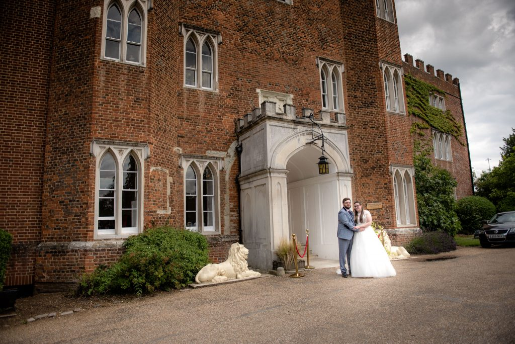 The bride and groom outside hertford castle