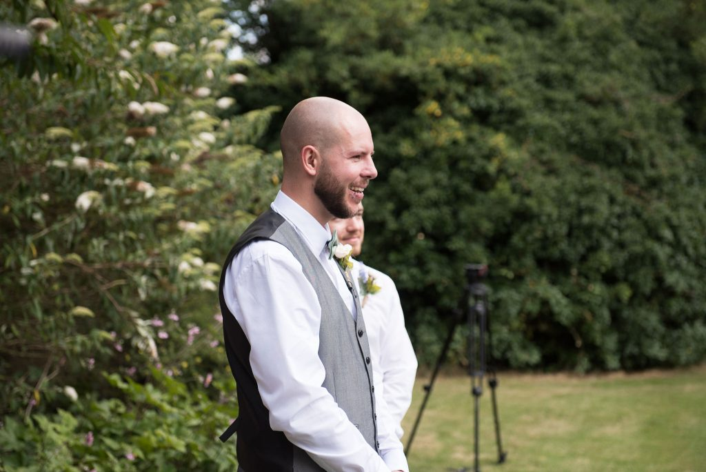 The groom smiles as he sees the bride for the first time