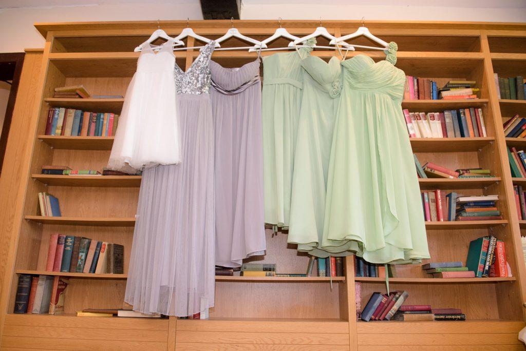 Bridesmaid dresses hanging on a bookshelf