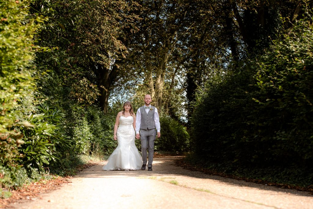 The bride and groom walk down the lane