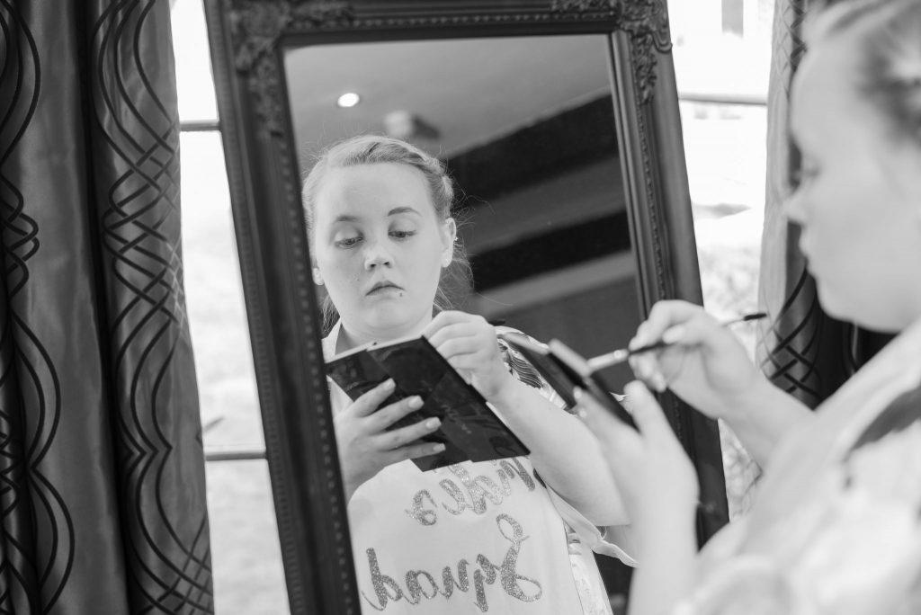 A bridesmaid applying her makeup