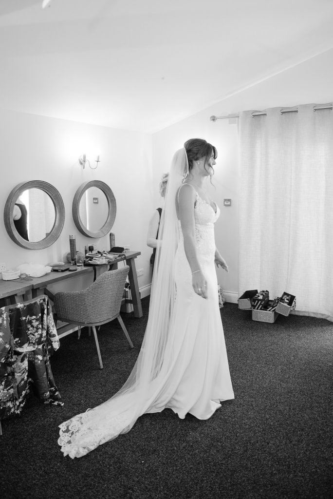 a black and white photo of the bride in her wedding dress