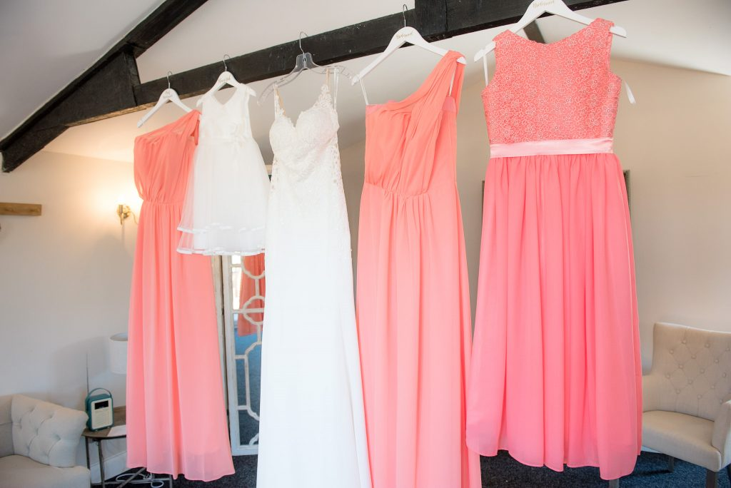 The bridal dresses hang from a wooden beam