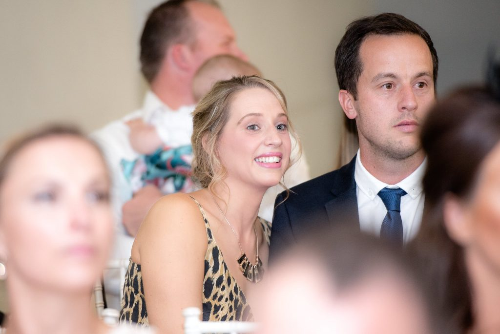 Wedding guests watch a slideshow of how the couple met