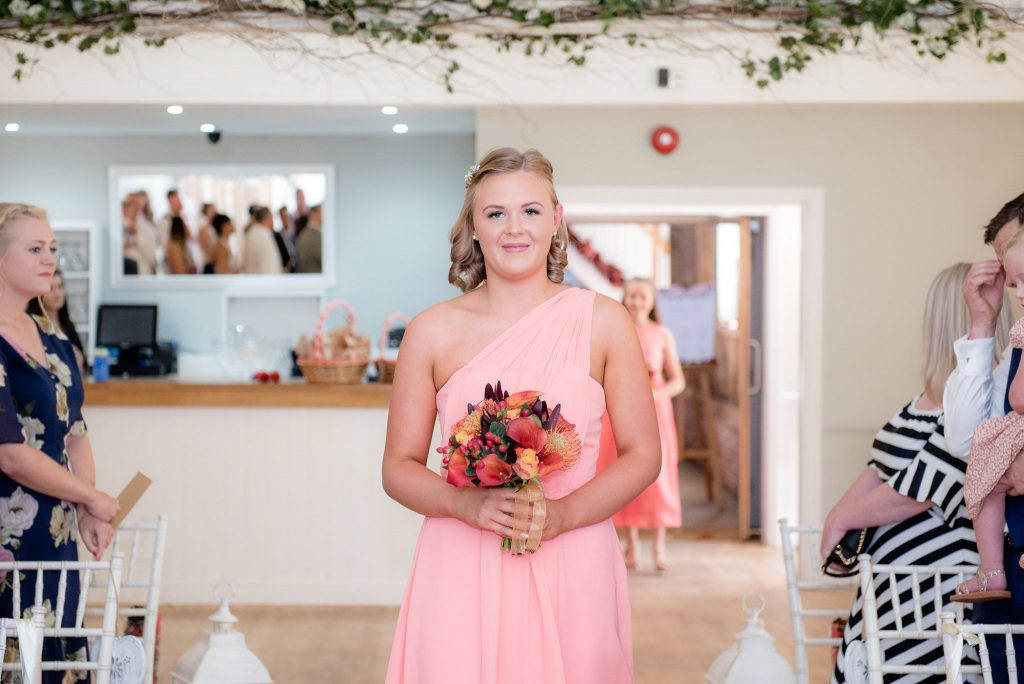 A bridesmaid carrying a bouquet of flowers