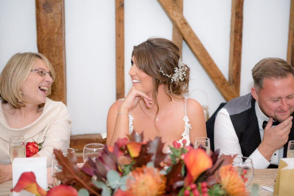 The bride sits amused at milling barn
