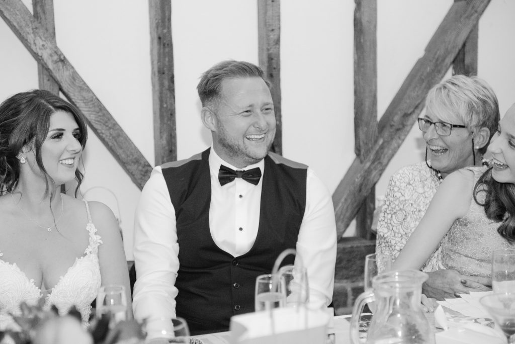 The groom laughs at with his wedding guests at milling barn