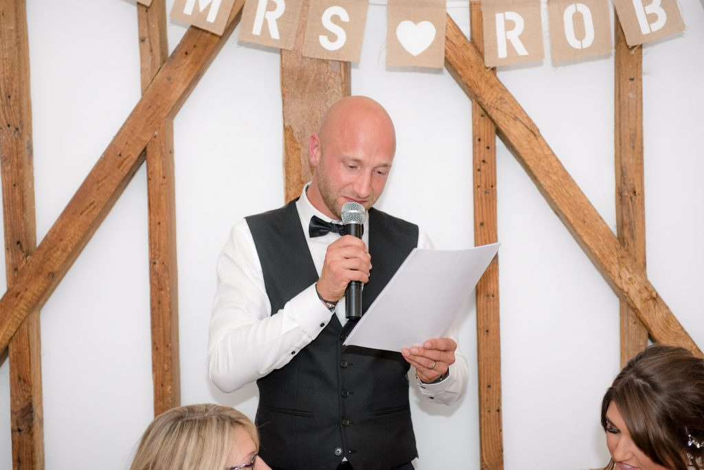 The best man gives his speech at this milling barn wedding