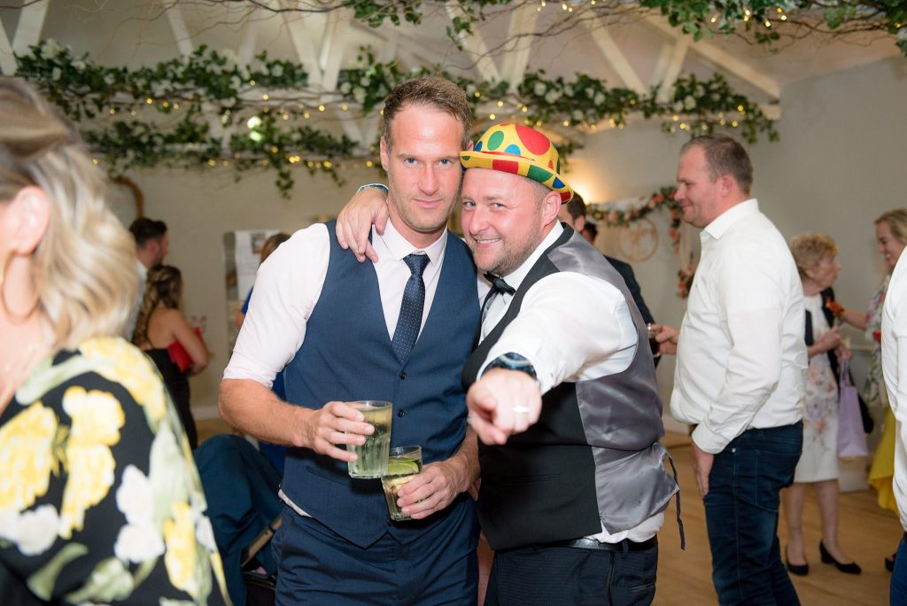 The groom has fun at his milling barn wedding