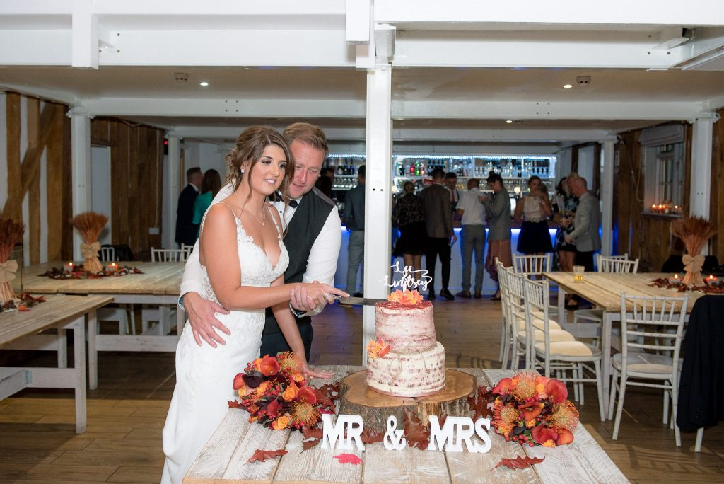 The bride and groom cut the wedding cake at Milling Barn