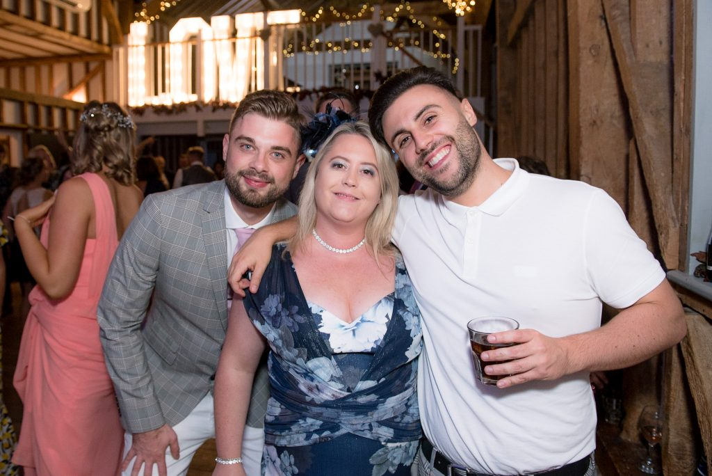 Three guests having fun at milling barn wedding venue