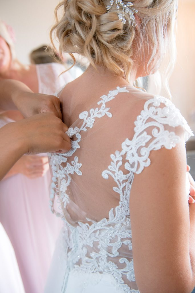 The back of the wedding dress being buttoned-up