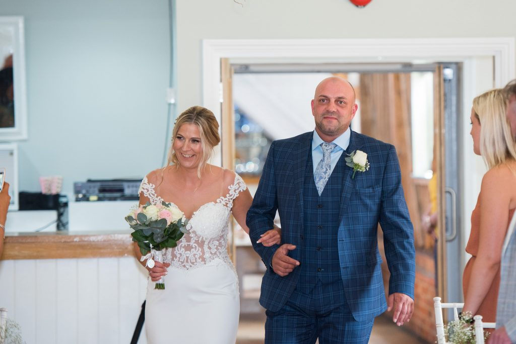 The proud brother walking his sister down the aisle