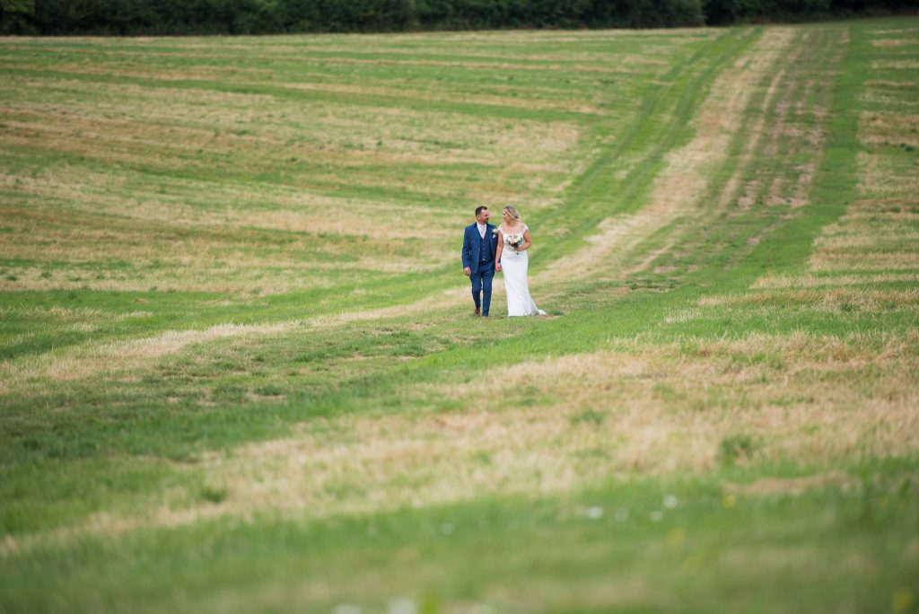 The bride and groom walking through fields