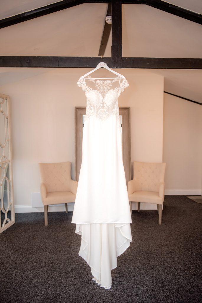A wedding dress hanging from a wooden beam