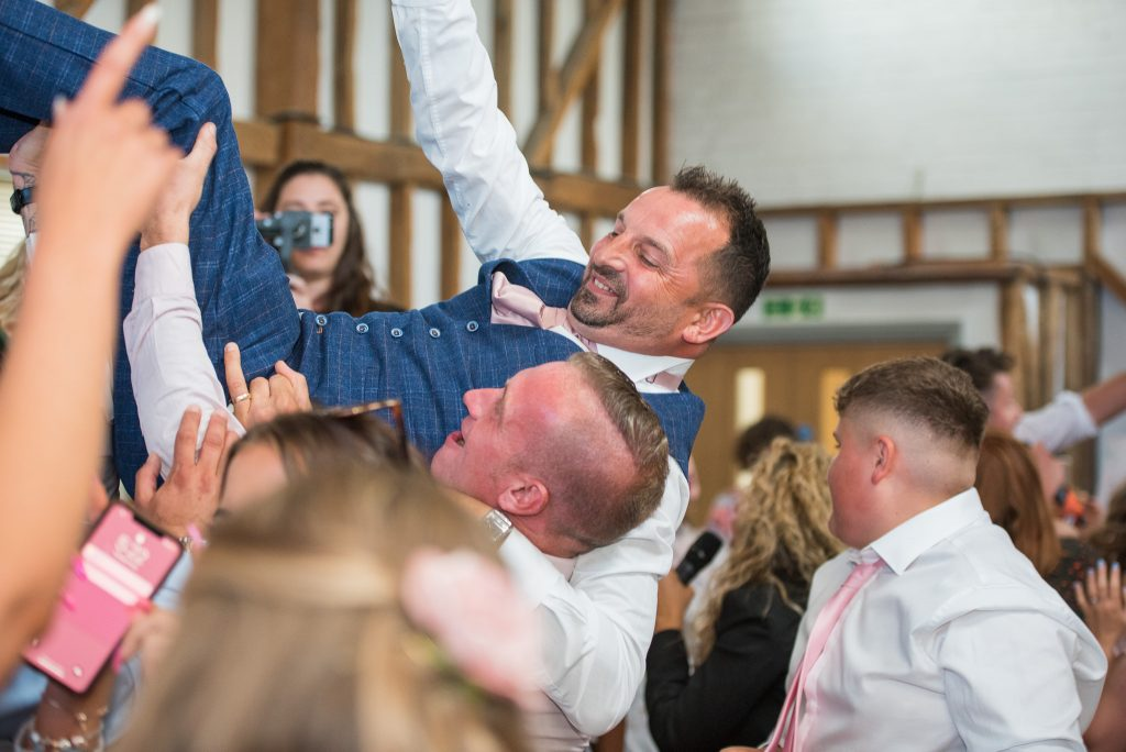 The groom being carried across the wedding venue