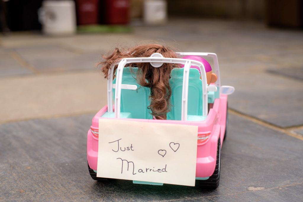 Barbie leaves with a just married sign on the back of the car