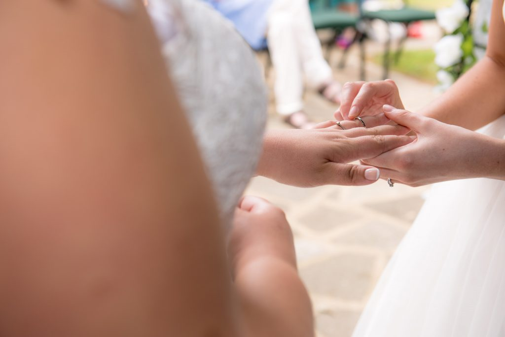 The two brides exchange wedding rings