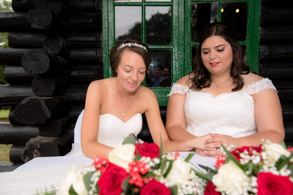 The two brides signing the wedding register