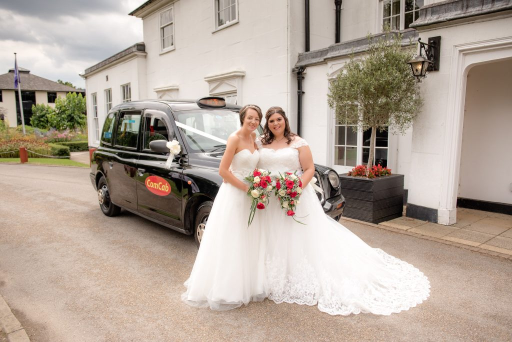 The two brides beside the london taxi