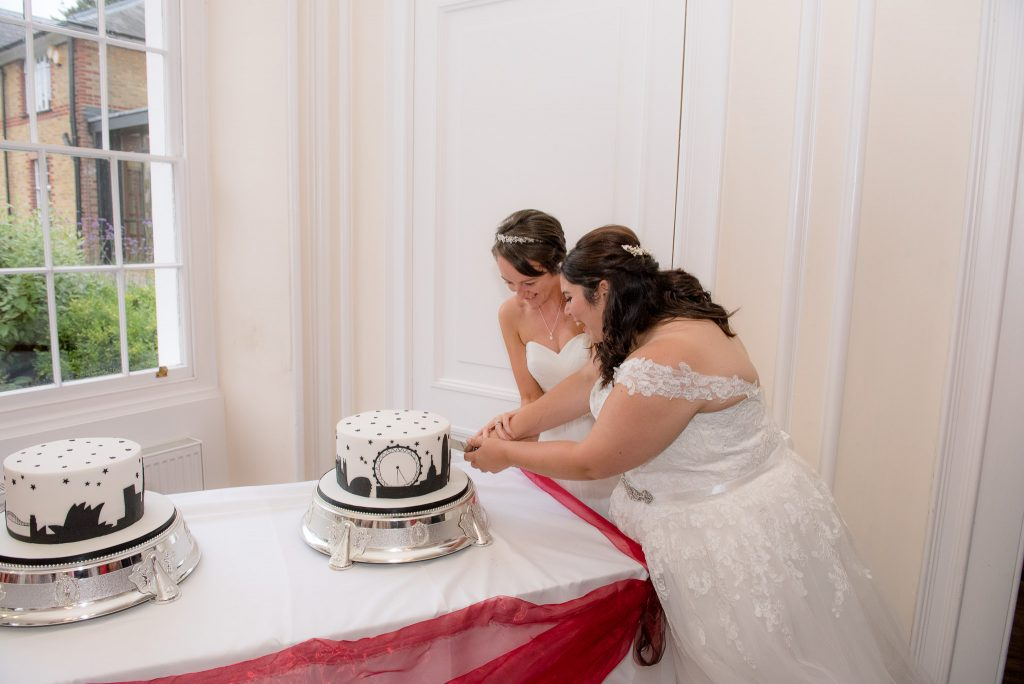 The two brides cut the wedding cake