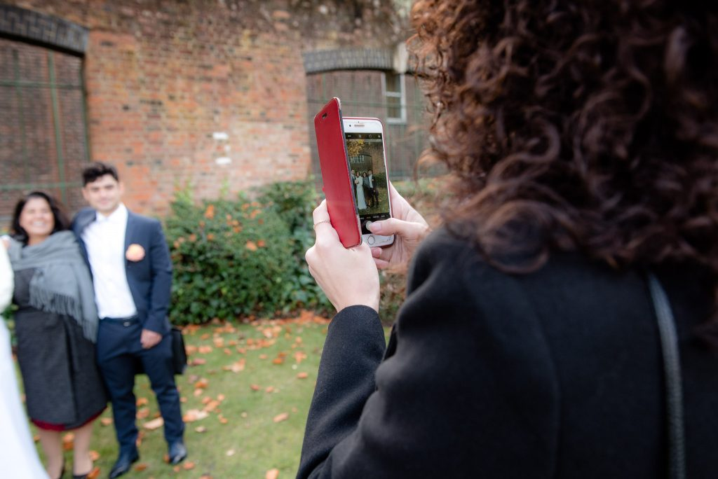 A guest takes a picture on her phone at St Albans Registry Office